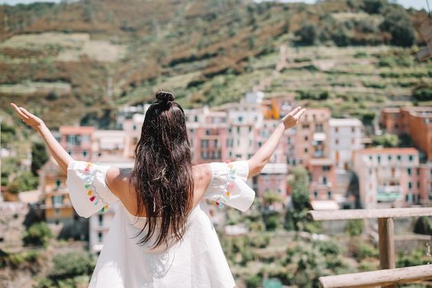 Vista posteriore della ragazza felice sfondo bella vista di manarola, cinque terre, liguria, italia