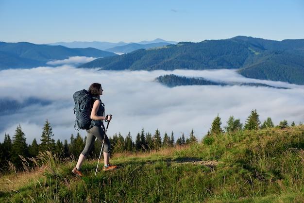 Vista posteriore della ragazza sportiva escursionista con zaino e bastoncini da trekking escursioni su sentiero rurale sulla cima di una collina, godendo foschia mattutina nella valle, foreste