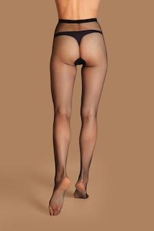 Vista posteriore delle gambe femminili sottili in calze a rete nere