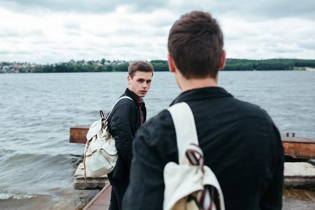 Vista posteriore di adolescenti in riva al lago