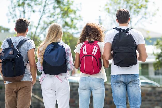 Vista posteriore di amici anca con zaini in piedi sulla strada