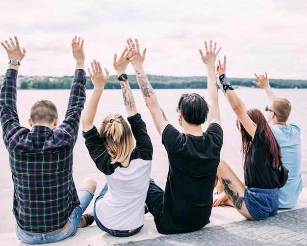 Vista posteriore di amici seduti vicino al lago alzando le mani