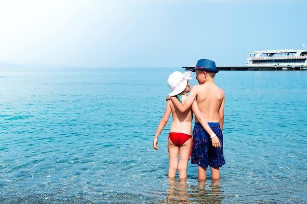 Vista posteriore di babygirl e babyboy baci sulla spiaggia in cappelli di paglia in riva al mare.