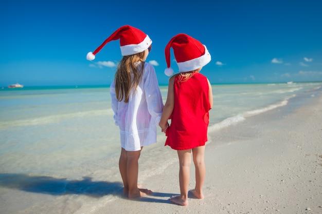 Vista posteriore di bambine carine in cappelli di natale sulla spiaggia esotica