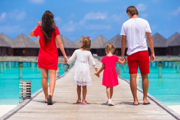 Vista posteriore di bella famiglia sul molo di legno durante le vacanze estive al resort di lusso