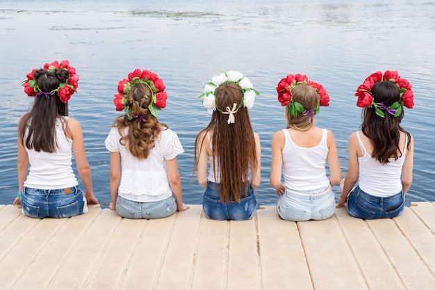Vista posteriore di cinque giovani donne, con ghirlande di fiori, jeans e magliette bianche