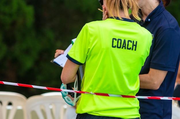 Vista posteriore di due allenatori di nuoto sportivo femminile discutendo sul gioco