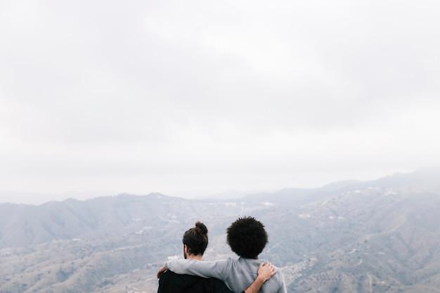 Vista posteriore di due escursionisti di sesso maschile che si affaccia sul paesaggio di montagna