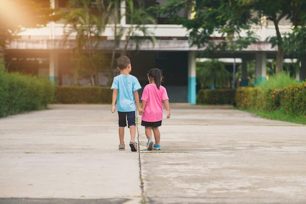 Vista posteriore di fratelli e sorelle camminano mano nella mano