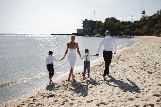 Vista posteriore di genitori e figli si tengono per mano insieme e camminano sulla spiaggia in una giornata di sole estivo, vestiti con abiti eleganti bianchi