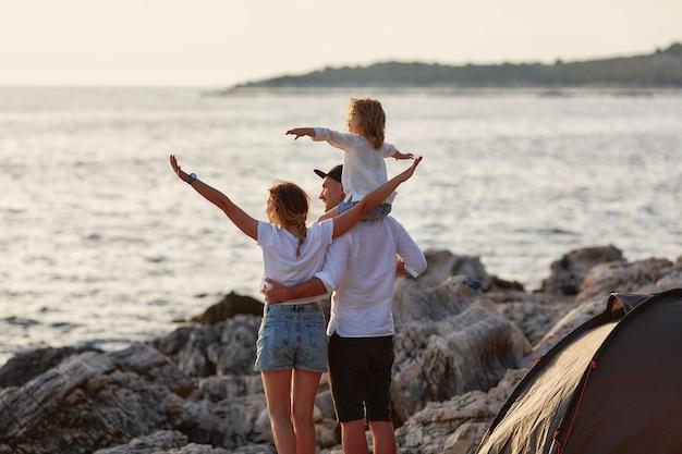 Vista posteriore di genitori felici con figlia piccola, seduto sul collo di papà e ammirando il tramonto sul mare vicino alla tenda. famiglia che abbraccia e punta a mano in mare e guarda da vicino.