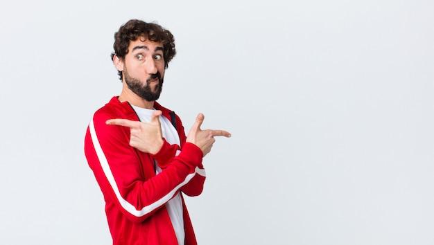 Vista posteriore di giovane uomo barbuto che sembra perplesso e confuso, insicuro e che punta in direzioni opposte con dubbi contro copia spazio muro
