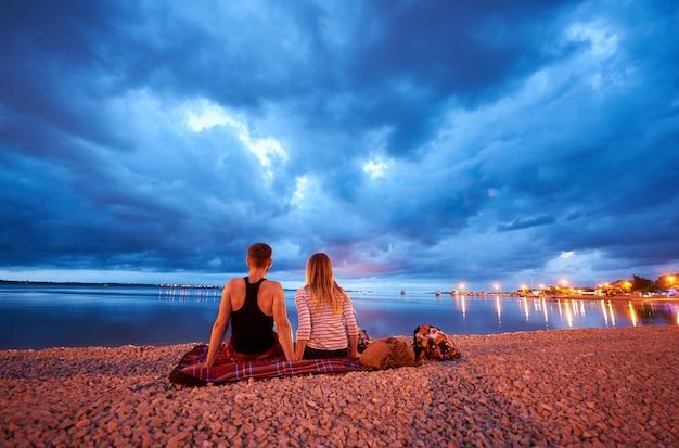Vista posteriore di giovane uomo e donna seduta sul tappeto sulla spiaggia di ciottoli della località turistica al crepuscolo, godendo della vista delle barche da crociera galleggianti in acque blu calme e drammatico cielo serale nuvoloso