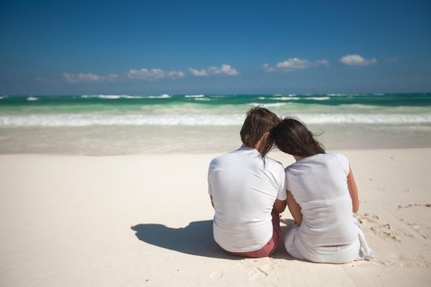Vista posteriore di giovani coppie alla spiaggia bianca tropicale