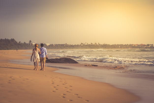 Vista posteriore di giovani coppie felici che camminano su una spiaggia tropicale deserta. foto tonificante