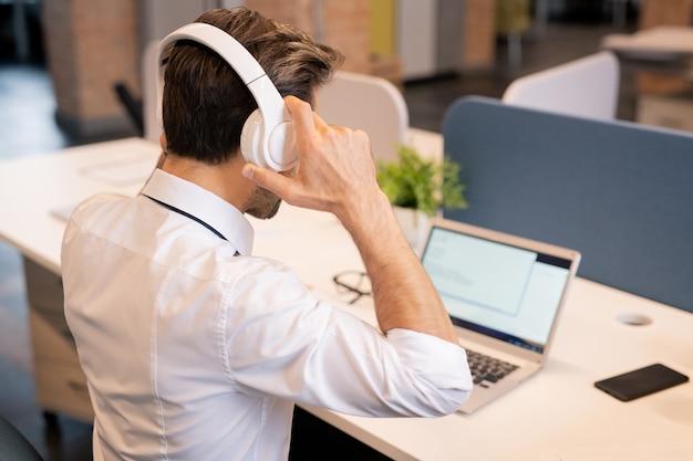 Vista posteriore di occupato giovane maschio manager del call center seduto alla scrivania con laptop e regolazione delle cuffie mentre si prepara per il lavoro