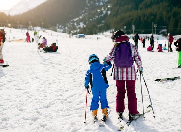 Vista posteriore di piccoli sciatori primi passi per imparare a sciare.