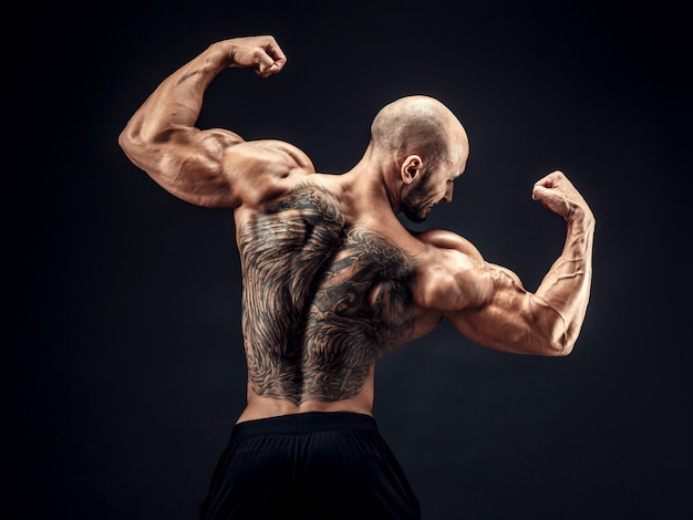 Vista posteriore di posa bodybuilder con tatuaggio posteriore