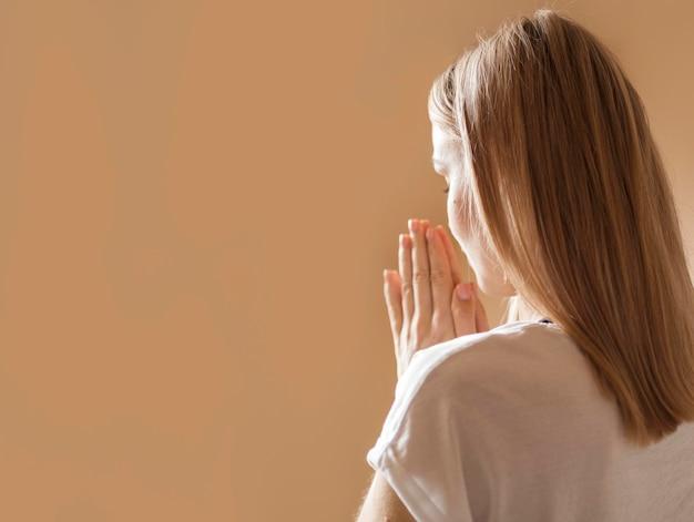 Vista posteriore di pregare della donna