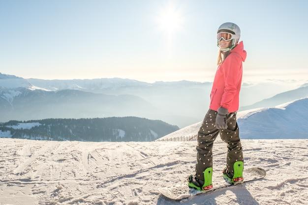 Vista posteriore di snowboarder femminile in piedi con lo snowboard e godersi il paesaggio di montagna. concetto di snowboard