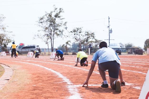 Vista posteriore di studenti pronti per iniziare a correre sulla pista di atletica