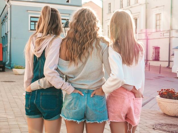 Vista posteriore di tre giovani amici di hipster femminili. ragazze vestite in abiti casual estivi. donne in piedi all'aperto. hanno messo le mani in pantaloncini nelle tasche posteriori. posa al tramonto