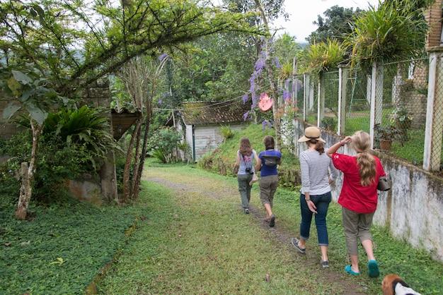 Vista posteriore di turisti che camminano in una fattoria, finca el cisne, honduras