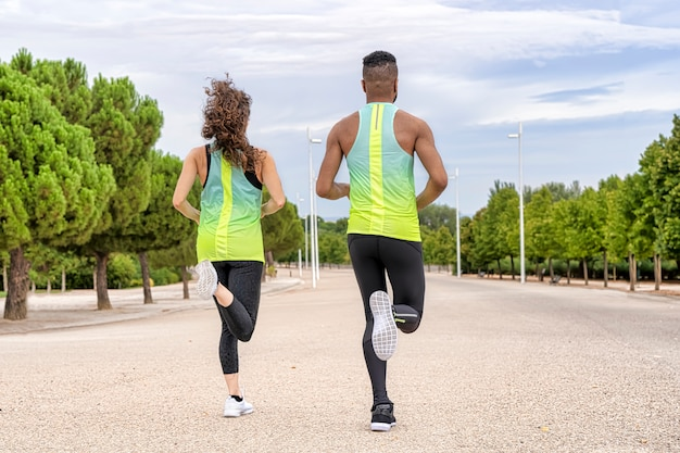 Vista posteriore di un paio di corridori di diversa etnia che corrono. l'uomo è nero e la donna bianca