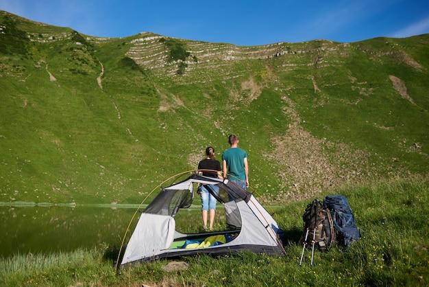 Vista posteriore di un ragazzo e una ragazza in piedi vicino al campeggio con una tenda, zaini e bastoncini da trekking, guardando una possente montagna verde ai piedi del quale è un lago sotto un cielo blu