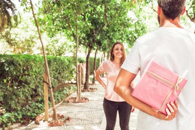 Vista posteriore di un uomo che nasconde il regalo di san valentino dalla sua fidanzata nel parco