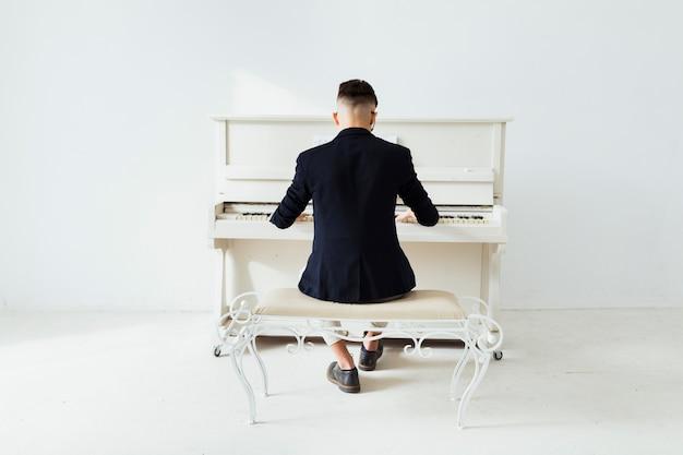 Vista posteriore di un uomo che suona il pianoforte seduto contro il muro bianco