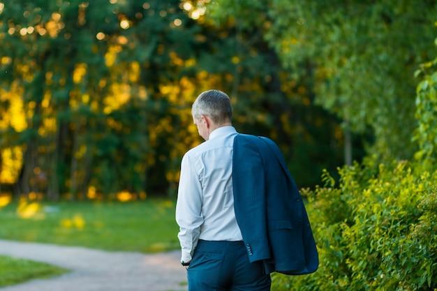 Vista posteriore di un uomo d'affari a piedi guardando nel parco