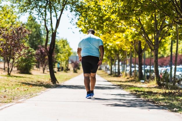 Vista posteriore di un uomo di colore anziano con problemi di sovrappeso in esecuzione nel parco