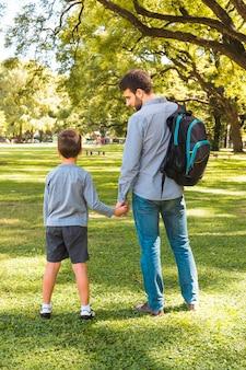 Vista posteriore di un uomo in piedi con suo figlio nel parco