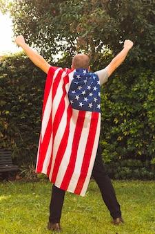 Vista posteriore di un uomo in piedi nel parco indossando la bandiera degli stati uniti capo alzando le braccia