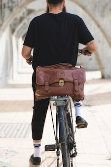 Vista posteriore di un uomo seduto sulla bicicletta con borsa marrone