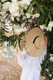 Vista posteriore di una bella ragazza in abito bianco e cappello di paglia.
