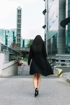 Vista posteriore di una donna d'affari che cammina sulla strada