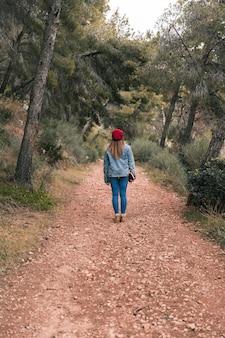 Vista posteriore di una donna in piedi sulla pista di montagna