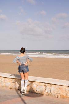 Vista posteriore di una femmina pattinatore con la mano sulla sua anca guardando il mare