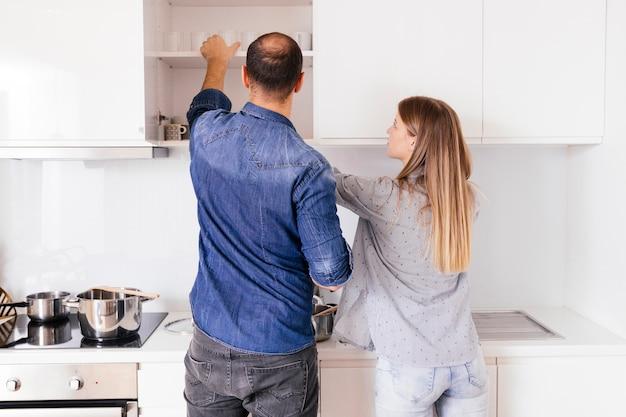 Vista posteriore di una giovane coppia di prendere gli occhiali dallo scaffale
