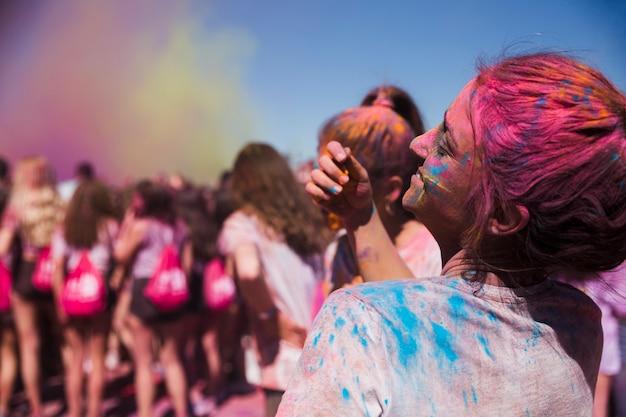 Vista posteriore di una giovane donna che gioca con la polvere di holi