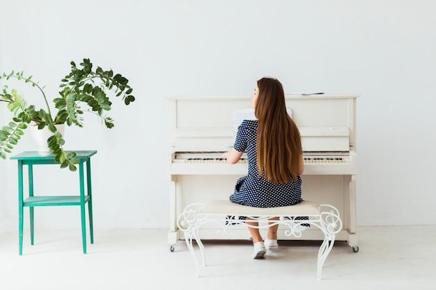 Vista posteriore di una giovane donna che suona il pianoforte contro il muro bianco