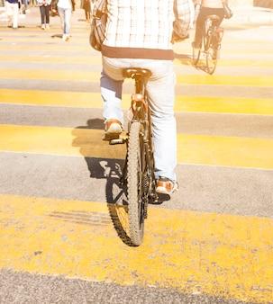 Vista posteriore di una persona che guida la bicicletta su una striscia gialla stampata su strada