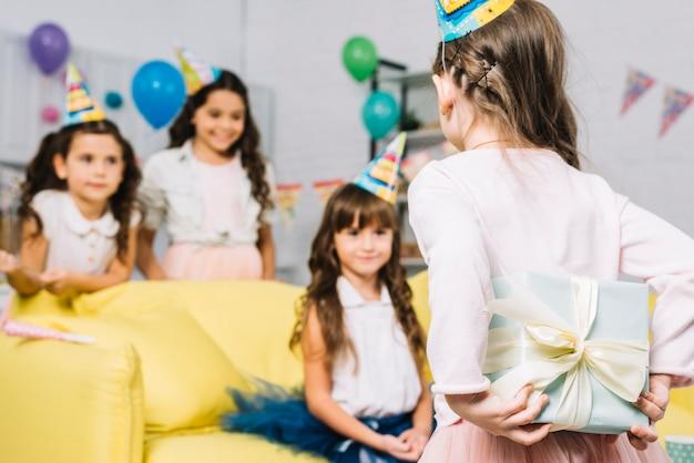 Vista posteriore di una ragazza che nasconde il regalo dal suo amico alla festa di compleanno