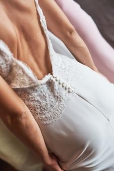 Vista posteriore di una sposa in un elegante abito da sposa bianco con schiena aperta.