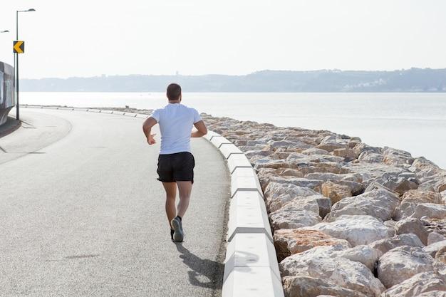 Vista posteriore di uomo forte che corre sulla strada del mare