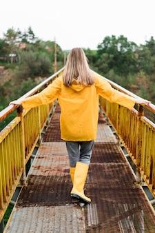 Vista posteriore donna bionda che indossa abiti da pioggia