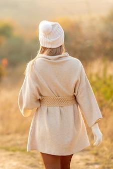 Vista posteriore donna bionda che indossa un berretto bianco