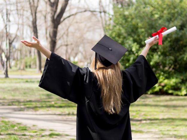 Vista posteriore donna che celebra la laurea